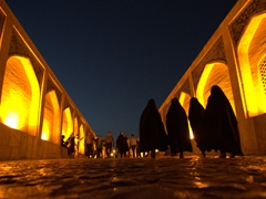 Chador covered women crossing the Khaju Bridge at night
