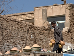 Collecting clay pottery to sell; Yazd old town