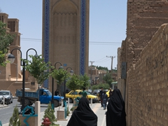 Chador clad women walking towards the Yazd clock tower