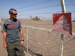 "Robby staring at a ""Danger - do not enter"" sign at the location of the ill fated US hostage rescue mission's crash site (24 April 1980); Tabas Desert"