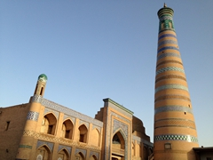 Admiring the orange glow of the setting sun on Islom-Hoja minaret, Uzbekistan's tallest at 57 meters in height; Khiva