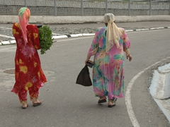 Colorfully dressed Uzbek women carrying their bazaar purchases