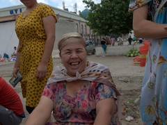 Awesome lady showcasing her gold grill at the bazaar; Samarkand