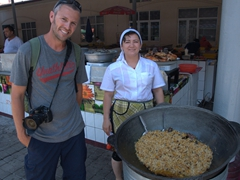Robby stands next to a massive vat of plov