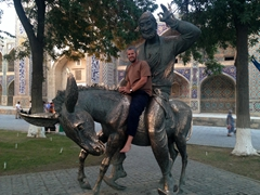 Robby poses with a statue of Nasreddin Hodja (13th century Sufi philosopher) on his donkey; Bukhara