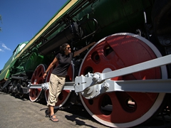 Becky showcases how massive this train's wheels are; Railway Museum in Tashkent