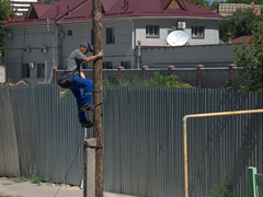 City worker climbing down a pole