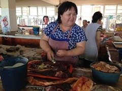 Kazakh lady smashing garlic into her sausages; Taraz Bazaar
