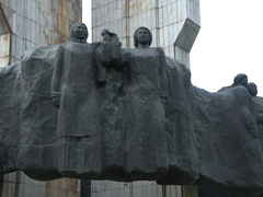 Russian and Kyrgyz mothers with their hands held together in a handshake; People's Friendship Monument