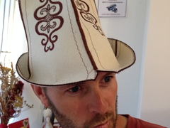 Robby models a traditional Ak kalpak (white felt hat)