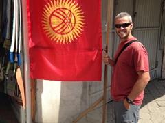 Robby stands next to a Kyrgyzstan flag; Osh Bazaar