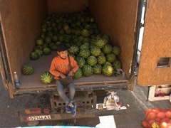 Young Kyrgyz boy selling watermelons by the roadside
