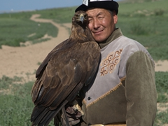 An eagle hunter lovingly caresses his bird; Bokonbaevo