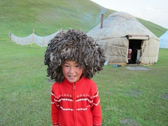 Young Kyrgyz girl modeling Robby's Uzbekistan sheep hat while her mother laughs nearby; Lake Son-Kul