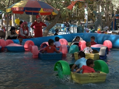 Kids enjoying a water ride at an amusement park near People's Square; Kashgar