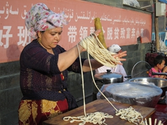 Uyghur woman making noodles; Kashgar night market