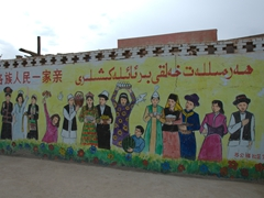 Chinese and Uigur script prominantly displayed on a wall mural - a common sight in Uigur-populated Turpan