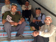 Uigur men posing for a photo; Turpan Bazaar