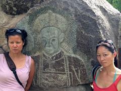 Becky and Ichi mimic a rock carving; Jiayuguan