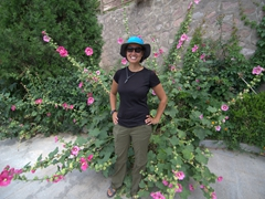 Becky stands next to an explosion of flowers; Bingling Thousand Buddha Caves