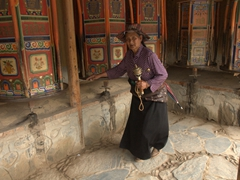 A pilgrim spins a small prayer wheel with her left hand and the massive prayer wheels with her right hand; Labrang Monastery