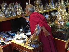 A monk shopping for a Buddha statue; Xiahe