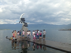 Locals gather around this statue at Qionghai Lake; Xichang