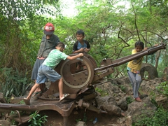 Kids play on a vintage machine gun (circa Vietnam War) in the woods of Mount Phousi; Luang Prabang