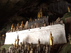 Hundreds of miniature Buddha sculptures laid out inside Pak Ou Caves