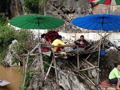 Vendors construct a rudimentary platform near the entrance to Pak Ou Caves