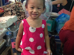 A cute girl smiles for the camera after we bought longan fruit from her mom (1 KG for 15,000 Kip); Phosy Market