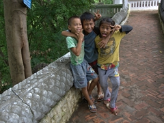 Playful Laotian children strike a pose; Mount Phousi