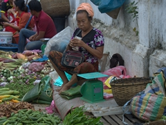 A vendor holds her money tight at the morning market in Luang Prabang