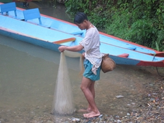A fisherman prepares to cast his net; Vang Vieng