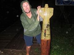 Robby strikes a pose next to a UXO on the toll bridge; Vang Vieng