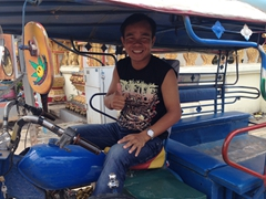 Our happy Jumbo tuk tuk driver as he patiently waits for us to visit the Golden Stupa; Vientiane