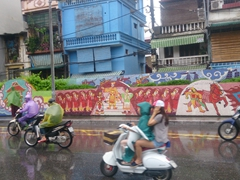 Motorcyclists zip by the world's largest ceramic mural just minutes before Typhoon Dianmu hits Hanoi