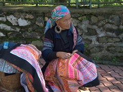An elderly woman works on a bed spread; Sapa