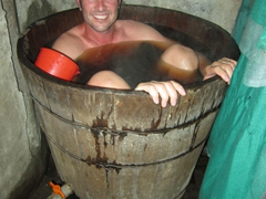 Robby soaking in his barrel tub full of herbal remedies to soothe our sore muscles; Ta Phin homestay