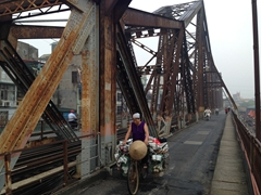 A vendor cycles across Long Bien bridge; Hanoi