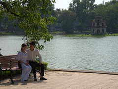 A young Vietnamese couple sits beside Hoan Kiem Lake (with Turtle Tower in the background); Hanoi