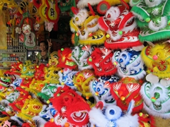 A friendly vendor flashes the peace sign beside the lion masks for sale to celebrate Chinese New Year; Hue