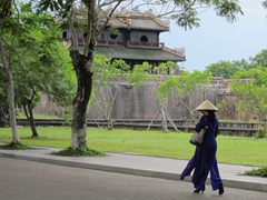 "A visitor wearing a Vietnamese ""Ao Dai"" visits the Imperial City in Hue"