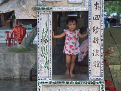 A young girl peers out from the Japanese Covered Bridge; Hue
