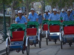 Eager cyclo drivers rush to the riverfront to greet arriving tourists; Hoi An