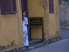 A traditionally dressed woman sneaks a peek around the corner; Hoi An