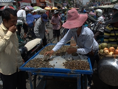 A man slurps down tasty snails from this market vendor