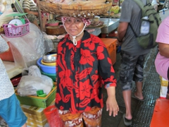 A Cambodian lady balances a basket of fish on her head; Phnom Penh central market