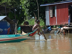 A young boy rows himself around a fishing village on the Tonle Sap river