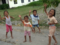 Exuberant girls shout out a warm greeting; Samosir Island